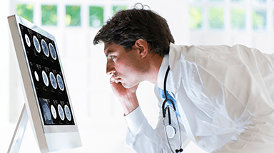 Doctor looking at image on computer.