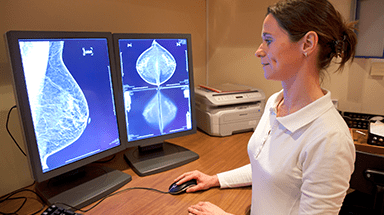 Health care provider viewing mammogram on computer screen