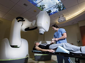Medical assistant preparing patient for CyberKnife treatment