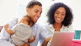 African American couple holding a baby and looking at the computer