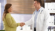 Pregnant woman meeting a doctor and shaking his hand