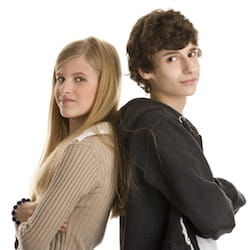 Girl and boy teens standing back to back