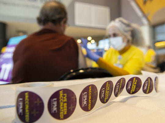 Image of vaccine stickers laying on table in front of a man receiving a vaccine shot.