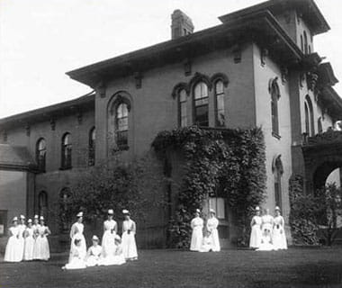 UPMC Chautauqua nurses gather on the lawn of the historic hospital building (circa 1897).