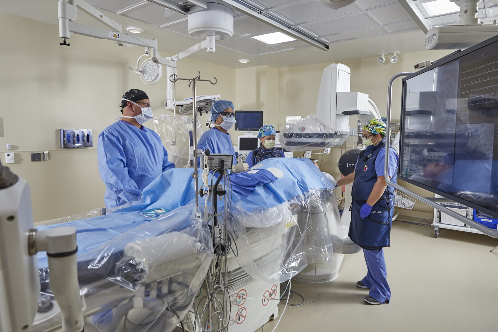 Image of a catheterization lab with 4 medical professionals providing treatment.