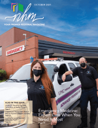 Two members, a woman and a man, of UPMC Passavant's Emergency Services team stand in front of an emergency vehicle, which is parked in front of the emergency department.