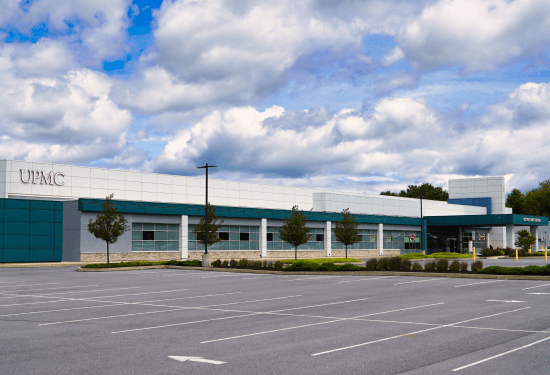 The exterior of UPMC Outpatient Center, formerly called Lebanon Valley Advanced Care Clinic. It is a long white and blue building. A small row of trees lines the parking lot in front of the building.