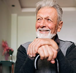 Older gentleman with his hands folded on top of one another, looking off into distance while smiling