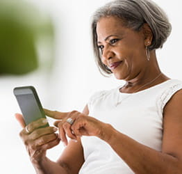A woman looking at her phone and touching the screen with her pointer finger.
