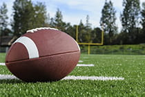 Close up photo of football sitting on a football field.